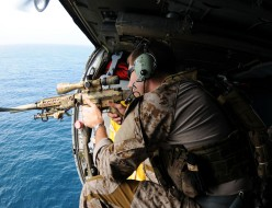 110822-N-XE109-945 ARABIAN SEA (Aug. 22, 2011) A Navy SEAL fires an MK-11 sniper rifle from an MH-60S Sea Hawk helicopter assigned to Helicopter Sea Combat Squadron (HSC) 9, deployed aboard the aircraft carrier USS George H.W. Bush (CVN 77), during a training flight. George H.W. Bush is deployed to the U.S. 5th Fleet area of responsibility on its first operational deployment conducting maritime security operations and support missions as part of Operations Enduring Freedom and New Dawn. (U.S. Navy photo by Mass Communication Specialist Seaman Apprentice Brian Read Castillo/Released)